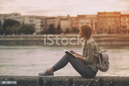 Woman thinking and writing at her notebook while sitting at the riverbank.Image is intentionally toned.