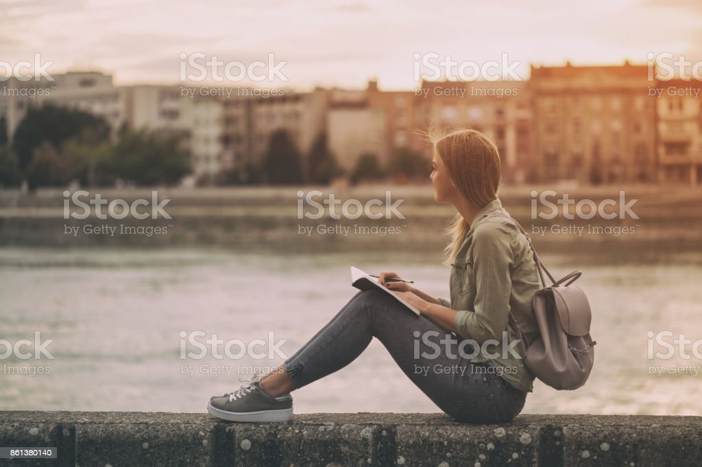 Woman thinking and writing at her notebook stock photo
