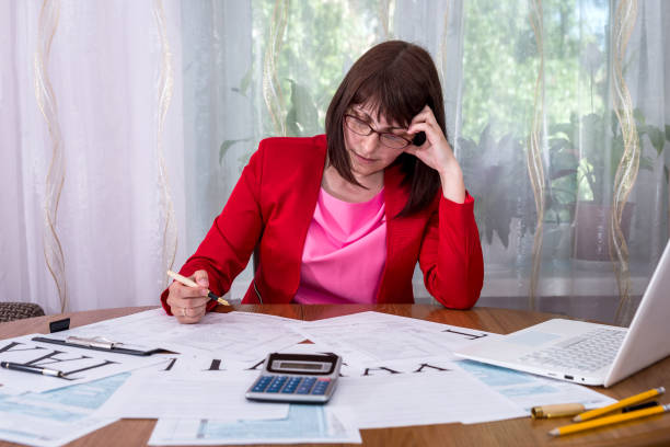 Woman thinking at 1040 tax form in office Woman thinking at 1040 tax form in office deem stock pictures, royalty-free photos & images