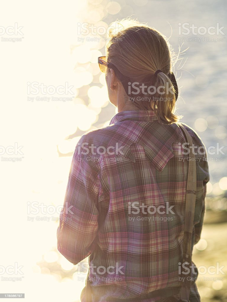 Woman thinking in golden afternoon light stock photo
