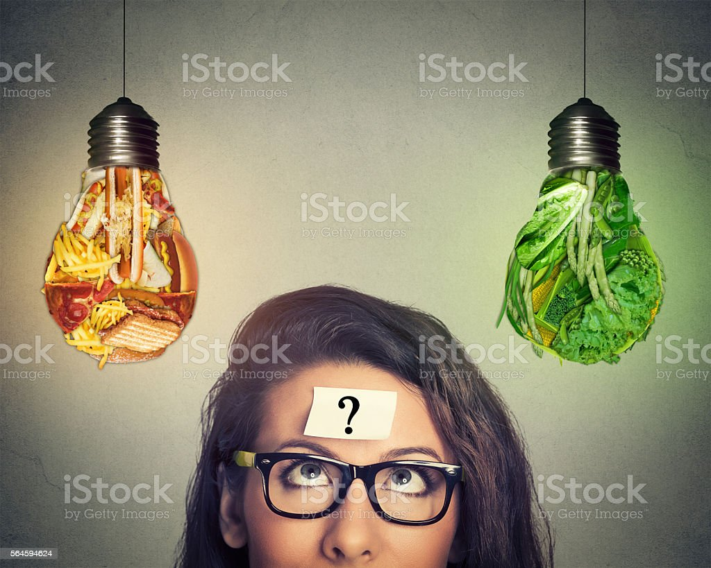 Woman thinking looking at junk food and vegetables light bulb stock photo