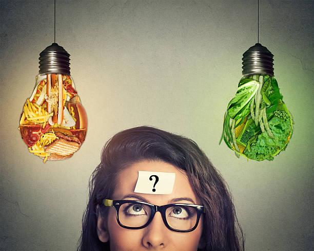 woman thinking looking at junk food and vegetables light bulb - trainingsplan frauen stock-fotos und bilder