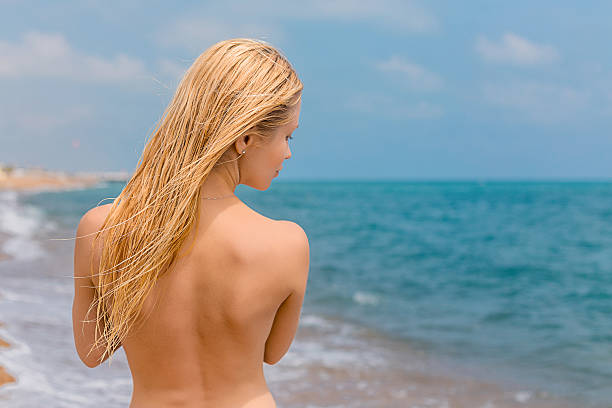 woman thinking on the beach - fkk strand stock-fotos und bilder
