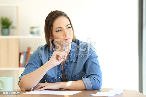 694187664istockphoto Woman thinking what to write in a letter 1030850552