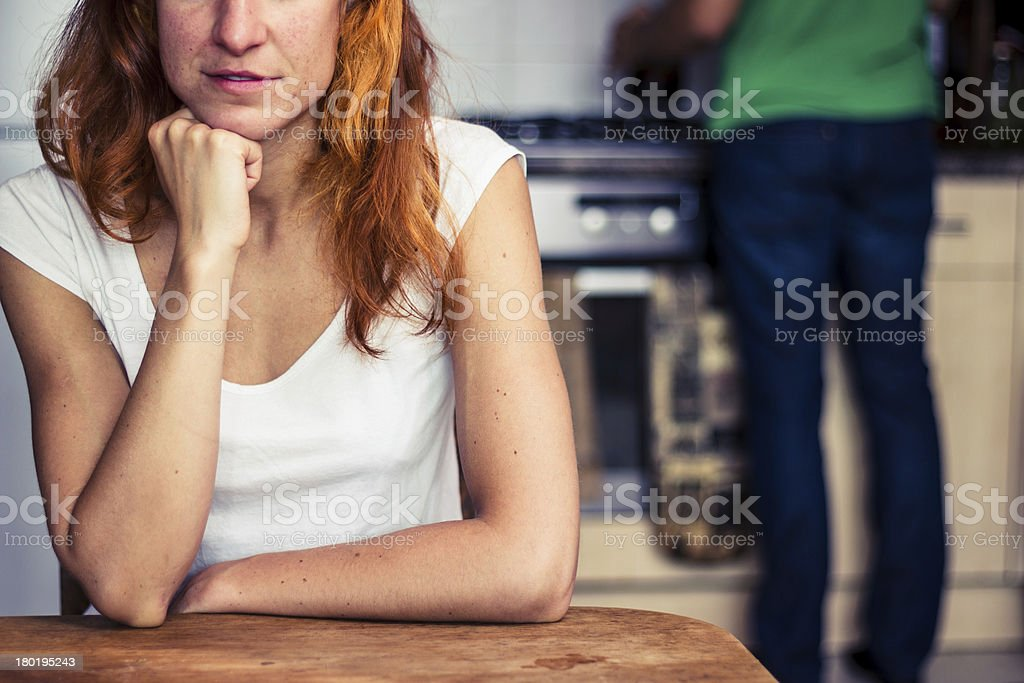 Woman thinking while her boyfriend is cooking royalty-free stock photo