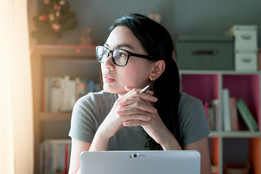 Woman thoughtful about work at home office desk laptop