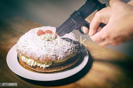 A woman threatens a delicious cream and raspberry cake with a toy gun at point blank range. Maybe something to do with weight loss or dietary problems; sugar, gluten, dairy. Only the hand of the woman is seen. Camera: 36MP Nikon D800E.