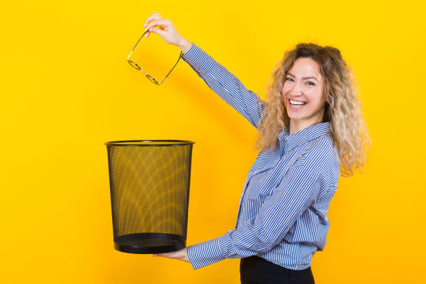 Woman throw away her glasses Portrait of curly-haired woman in striped shirt isolated on orange background throwing glasses she doesn't need any more into trash bin surgical correction of eyesight concept. throwing stock pictures, royalty-free photos & images