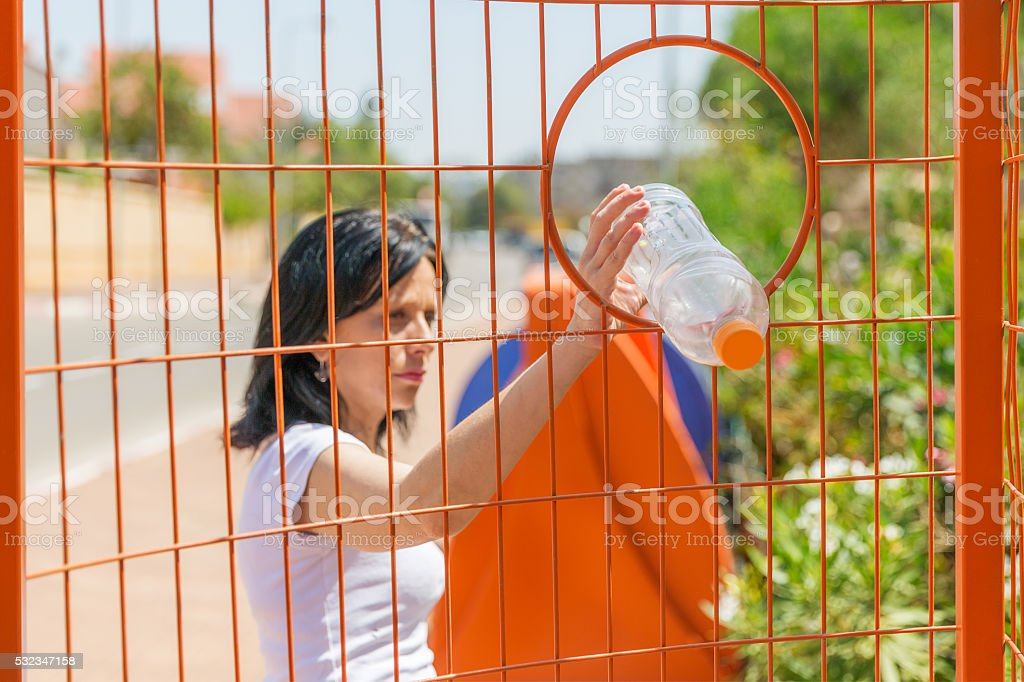 Woman throwing a bottle into trash bin for plastic products stock photo