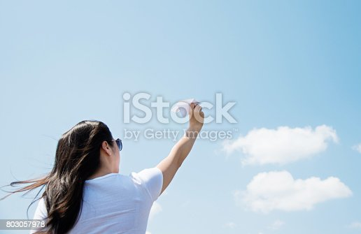 istock Woman throwing a paper airplane 803057978