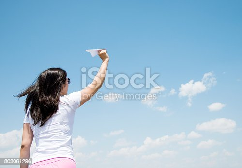 istock Woman throwing a paper airplane 803061296