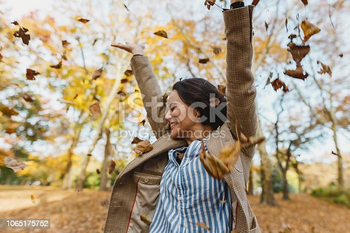 istock Woman throwing autumn leaves in Central Park 1065175752