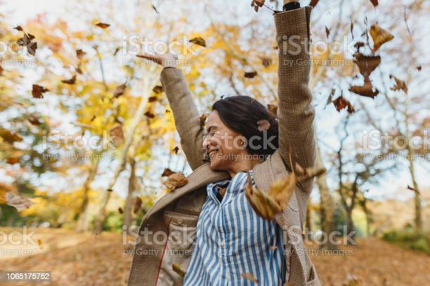 Photo of Woman throwing autumn leaves in Central Park