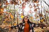 Woman throwing autumn leaves in Central Park stock photo
