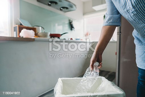 Woman throwing away a plastic bottle