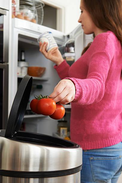 woman throwing away out of date food in refrigerator - food waste bildbanksfoton och bilder