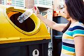 istock Woman throwing bottle in recycling bin. 1226974643