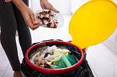 istock Woman Throwing Cake In Trash Bin 1093972240