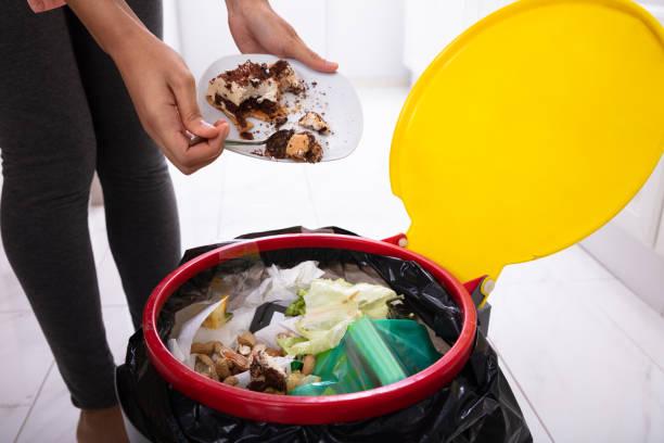 kvinnan kastar tårta i papperskorgen - food waste bildbanksfoton och bilder