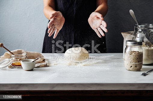istock Woman throwing dough on flour over marble counter 1225036926