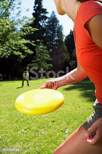 620402800istockphoto Woman throwing flying disc 521204248