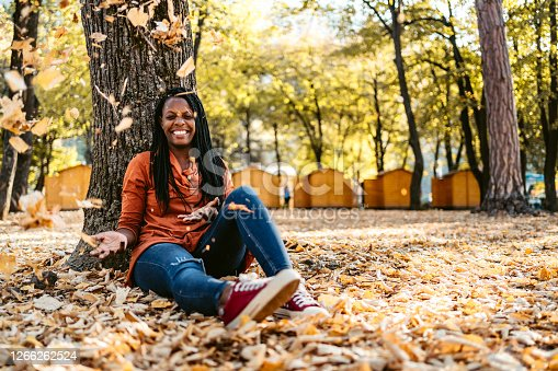 Carefree young smiling African-American woman sitting on a ground in a public park throwing autumn leaves. Day time.