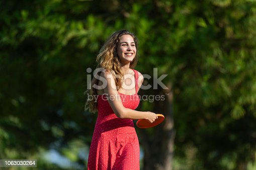 Woman throwing orange flying disk outdoor shot