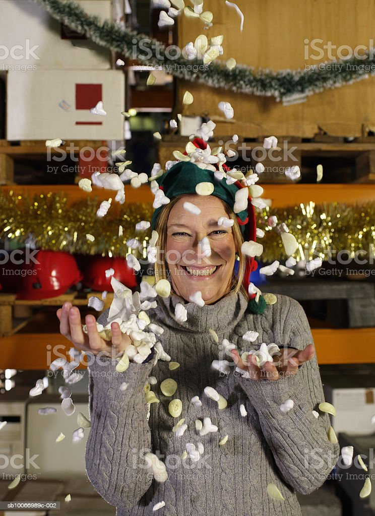 Woman throwing packing chips in air, portrait royalty-free stock photo