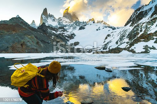 Young Caucasian woman throwing rocks in lake near Fitz Roy mountain in Patagonia
