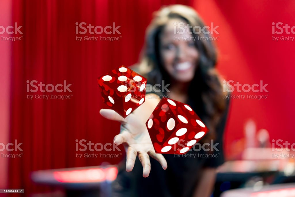 Woman throwing the dice at the casino stock photo