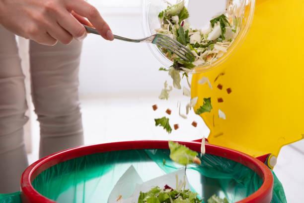 femme jeter les légumes dans la poubelle - dechets photos et images de collection