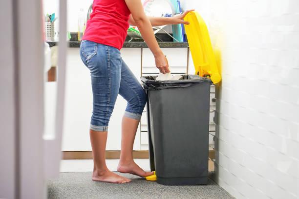 Eine Frau wirft Müll in den Müll in der Küche. – Foto