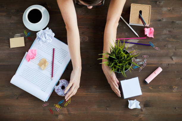 Woman Tidying Up Office Desk Directly above view of unrecognizable woman sorting out mess on working table, moving stationery, documents, food and plant order stock pictures, royalty-free photos & images