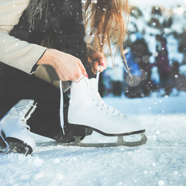 Woman tie shoelaces figure skates at ice rink close-up Woman tie shoelaces at figure skates at ice rink close-up, ice skating ice rink stock pictures, royalty-free photos & images