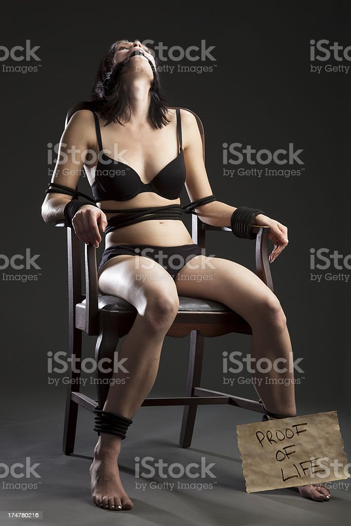 Woman Tied-Up, Held Hostage With Proof of Life Sign stock photo