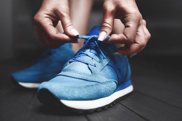 woman ties up shoelaces on sneakers. close up view. healthy lifestyle concept. the girl measures new sports sneakers in the dressing room. - tied up stock pictures, royalty-free photos & images