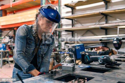 Female welder working in her workshop using an angle grinder. Los Angeles, America. October 2016