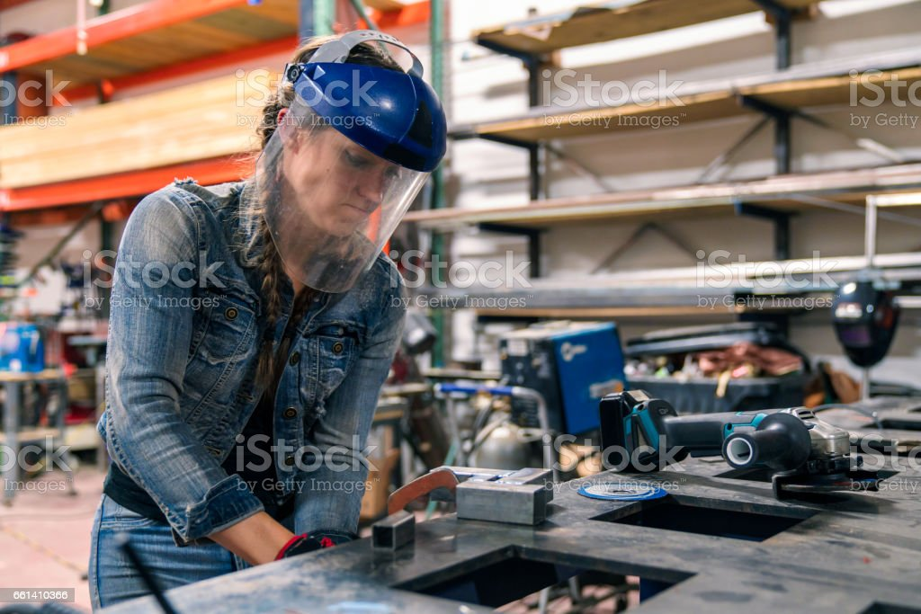 Woman tightening a vice to secure metal in place stock photo