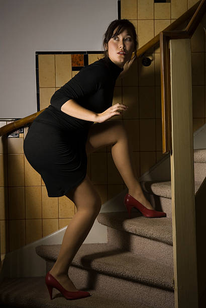 Woman Tiptoeing Up the Stairs stock photo