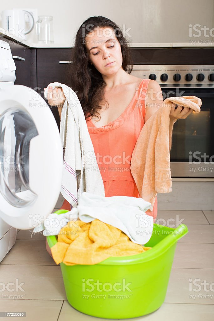 Woman  tired and washing clothes in machine stock photo