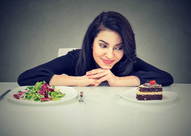 kvinna trött på diet restriktioner beslutar om att äta hälsosam mat eller söt kaka hon är sugen - cravings bildbanksfoton och bilder