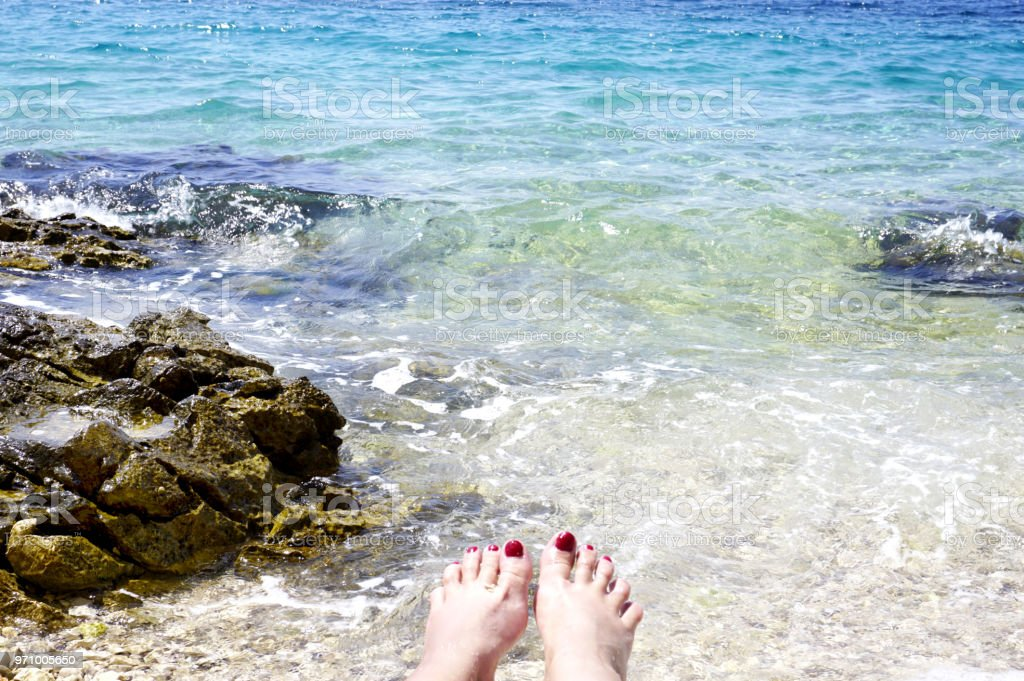 Woman toes in the blue lagoon in the Adriatic sea stock photo