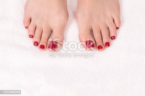Woman toes with classic glossy red pedicure on white terry towel, close up. Female bare feet. Spa, treatment, beauty shop, salon, massage and body care concept