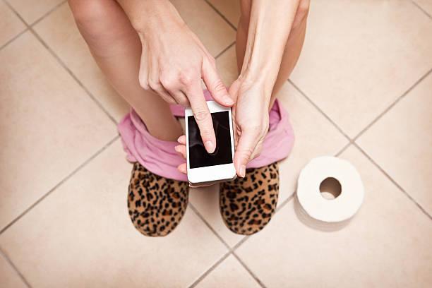 woman toilet texting - cell phone toilet stockfoto's en -beelden
