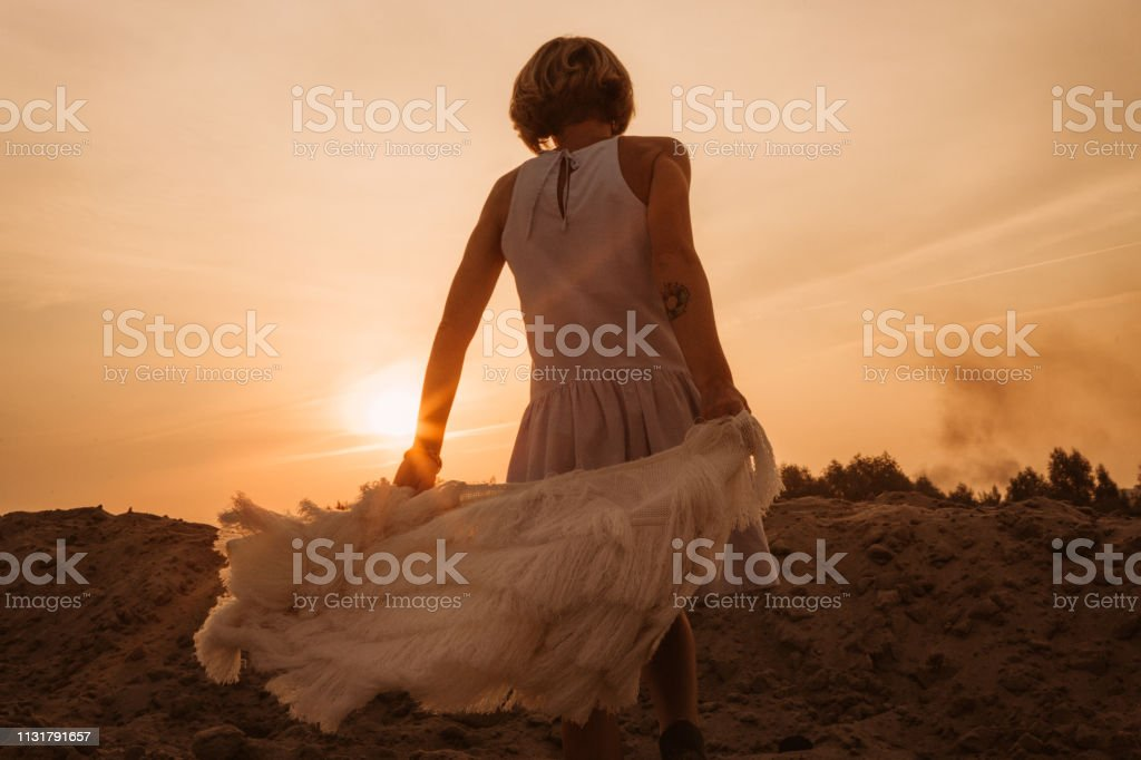 woman on top of the mountain rejoices and dances at sunset
