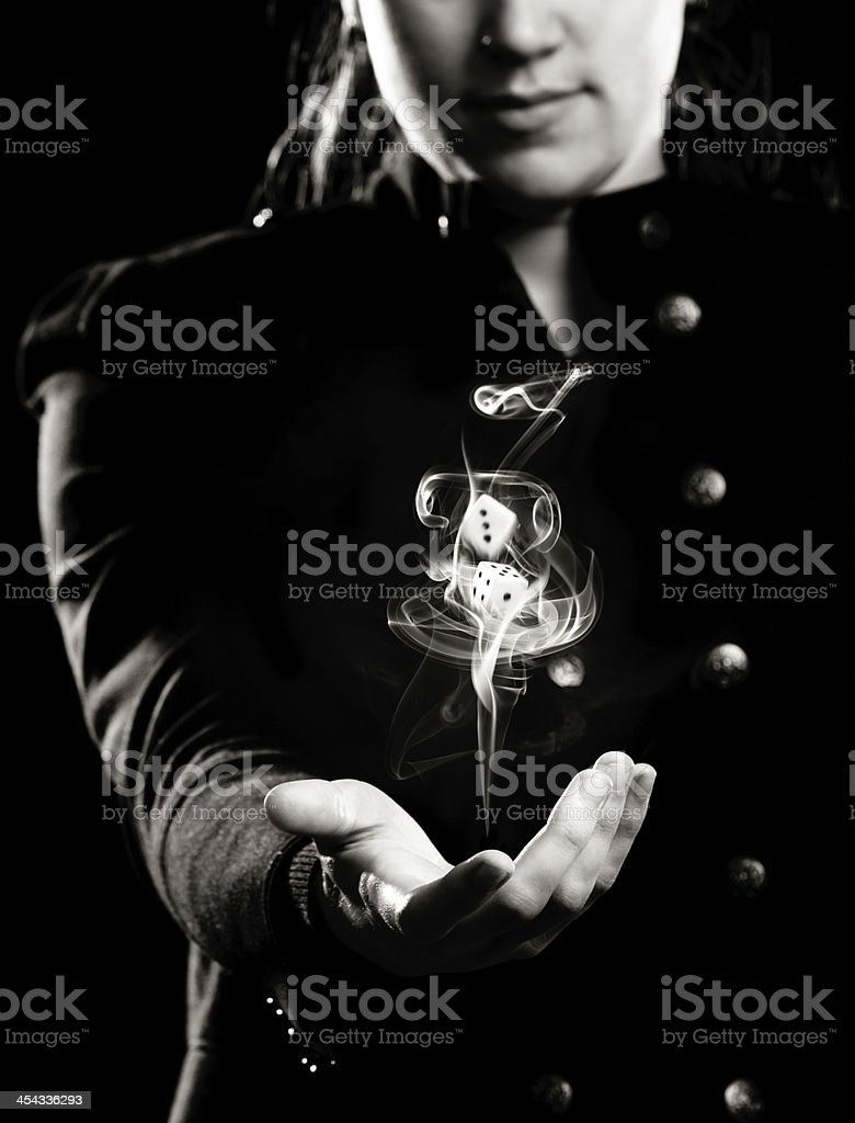 Woman tosses dice in smoke swirl: luck is a toss-up! royalty-free stock photo