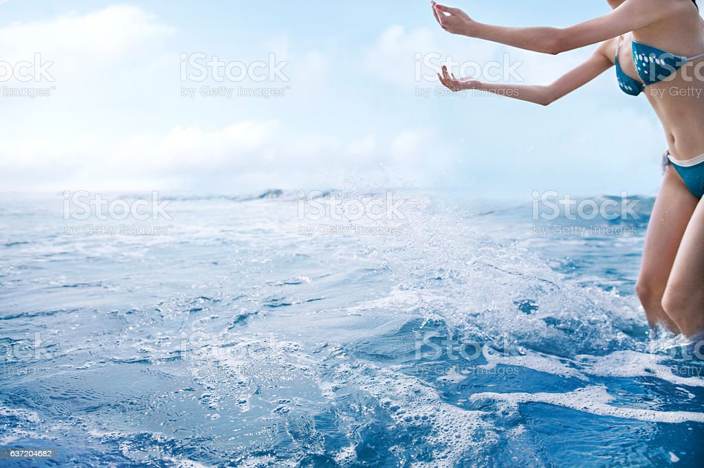 Woman tossing water into air at the beach stock photo