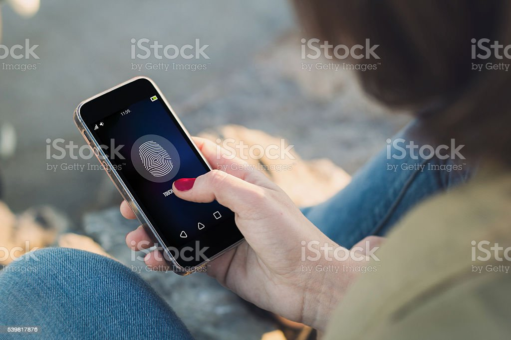 Woman touch the screen of her smartphone unlocking stock photo