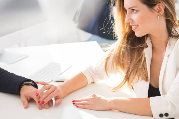 Woman touching a man Woman touches hand of a man in the office temptation stock pictures, royalty-free photos & images