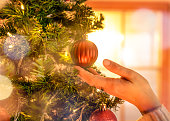 Close up photo of a woman's hand touching decorative ball hanging from the christmas tree in the middle of the living room.